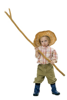 Country boy in straw hat, rubber boots and a long stick in his hand